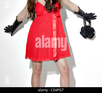 Woman in red dress back gloves and black handbag - Stock Photo