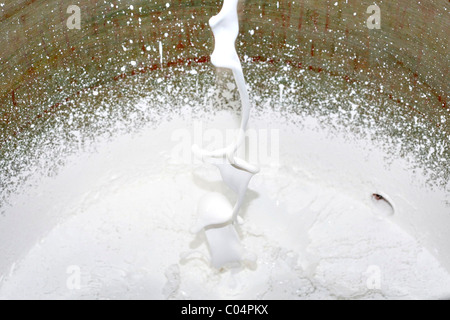 Flow of white paint falls into a bucket - Stock Photo