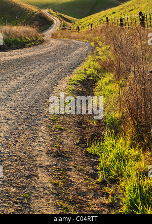 A rural road winds into the distance - Stock Photo