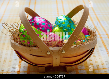 Small traditional wooden basket filled with hay and colorful wrapped chocolate easter eggs on a yellow and white - Stock Photo