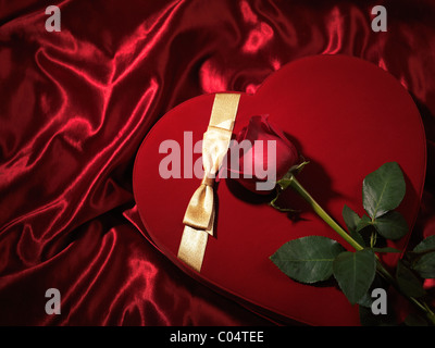 Red heart-shaped gift box and a red rose - Stock Photo