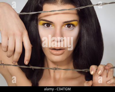 Artistic expressive beauty portrait of a young beautiful woman behind barbed wire - Stock Photo