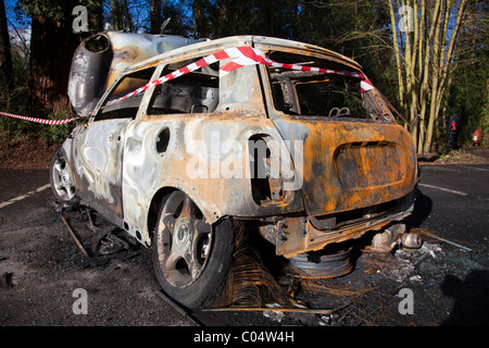 Burnt-out Mini car in a car park, probably abandoned and vandalised by joy riders, Kent, UK - Stock Photo