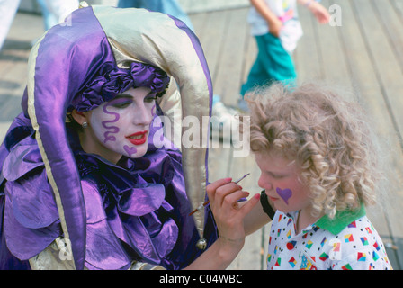 Face Painting - Clown paints Hearts on Face of Young Girl Child - Stock Photo