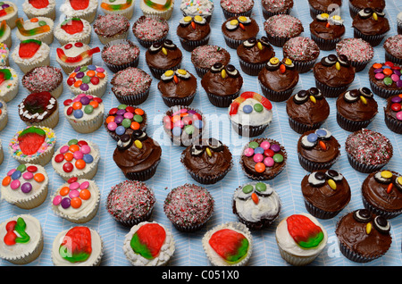 Decorated home made cupcakes on a table for a large party - Stock Photo