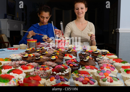 Two teenage girls decorating home made cupcakes on a table for a large party - Stock Photo