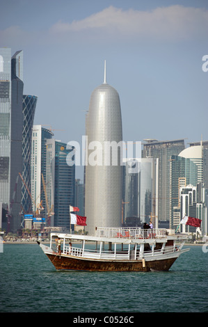 Traditional arabic Dhow boat on the Corniche Sea - Doha City Skyline, Qatar - The Doha 9 High Rise Office Tower - Stock Photo