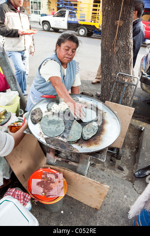 busy genial Mexican cook in spotless blue gingham apron working over her grill of blue corn tacos on sidewalk  of - Stock Photo