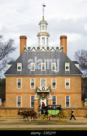 A coachman driving tourists by the Governor's Palace adorned with Christmas decorations in Historic Colonial Williamsburg, - Stock Photo