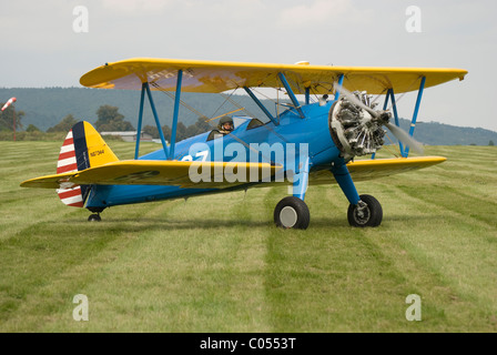 Biplane with radial engine - aircraft of type Boeing Stearman E75 on the ground, taxiing. - Stock Photo