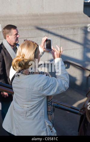 Brunette young lady or girl or woman tourist takes photo of London Eye from Westminster Bridge stairs on mobile - Stock Photo