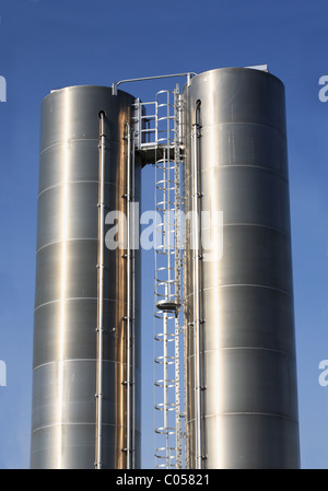 Two stainless steel chemical storage tanks against a blue sky, Seaham industrial estate, north east England - Stock Photo