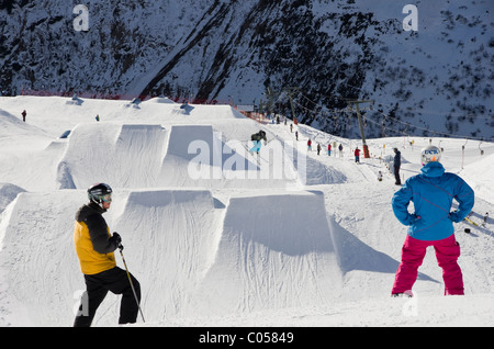Snowboarder and skier above ski jumps in Stanton Park funpark on Rendl. St Anton am Arlberg, Tyrol, Austria, Europe. - Stock Photo