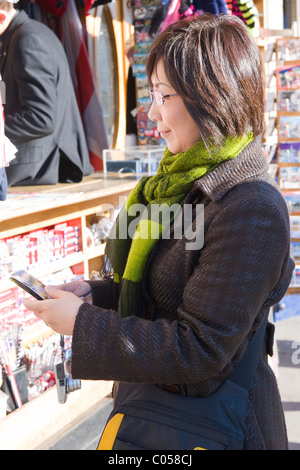 London , Westminster , pretty young brunette oriental girl or lady or woman , looks at photos on iPhone by souvenir - Stock Photo