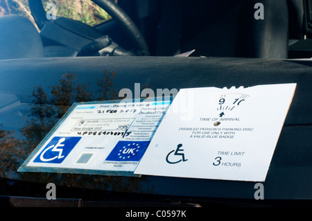 A 'blue badge' disabled parking permit on a car windscreen - Stock Photo