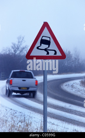 car travelling in winter snow passing warning sign of icy road near Leeds Yorkshire UK - Stock Photo