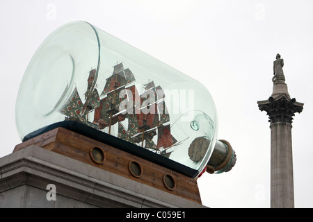 A model of 'The Victory' in a bottle on a plinth in Trafalgar Square, London, with Nelsons column in the background - Stock Photo