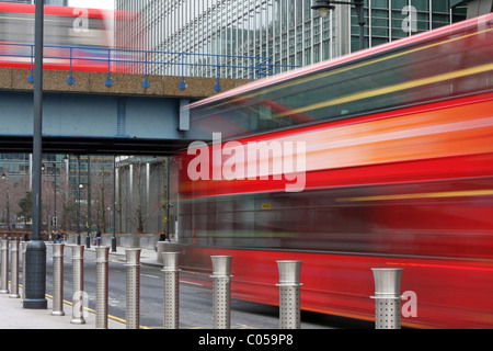 A blurred bus going under a bridge and a blurred DLR train going over the bridge in London's Canary Wharf - Stock Photo