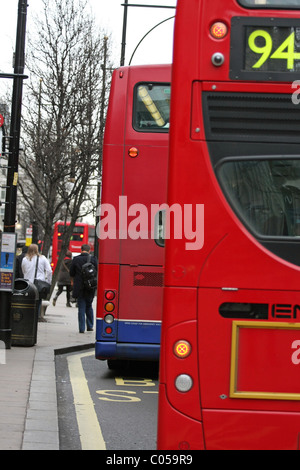 Two buses leaving a bus stop in Oxford Street, London - Stock Photo