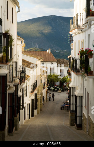 Typical traditional Spanish cobbled back street / streets / road & buildings & blue sky in the white village of - Stock Photo
