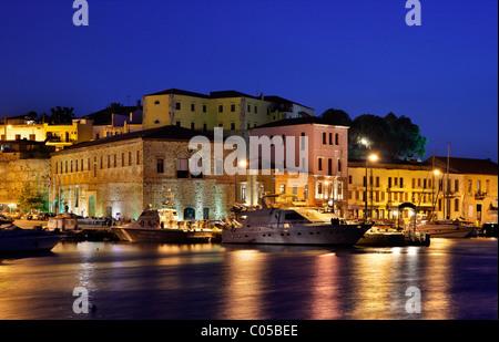Night view of the 'Big Arsenal' and Kastelli neighborhood, in the old Venetian port of Hania, Crete, Greece - Stock Photo