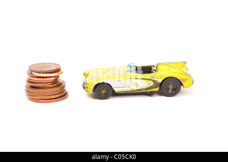 Old toy Corvette car with pile of penny pennies coins the cost of motoring - Stock Photo