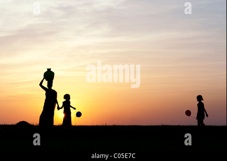 Indian Mother Carrying Water Pot With Children And Balloons In The Countryside Silhouette