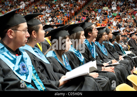 High school seniors in caps and gowns sitting in a row wait to receive their diplomas during graduation ceremony - Stock Photo