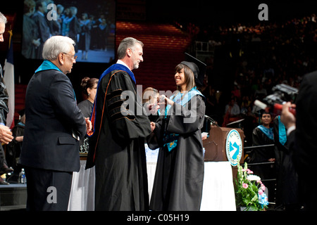 Hispanic teenage girl receives her diploma during graduation ceremony for Mission Early College High School in El - Stock Photo