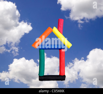 Funny house made from colorful plasticine on sky background - Stock Photo