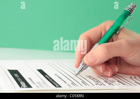Green Themed Pen in Hand Completing Form - Stock Photo