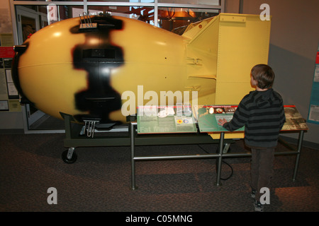 A model of the Fat Man atomic bomb dropped on Nagasaki, Japan in 1945.  Child is looking at the bomb and reading - Stock Photo