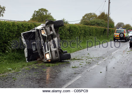 A four wheel drive car on its side after being involved in an accident - Stock Photo