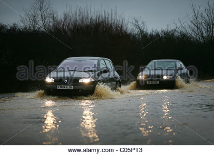 Cars making their way through flood waters in Essex - Stock Photo