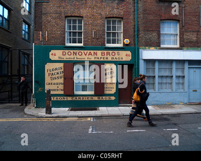 Two young women walking past Donovan Bros Paper Bag shop in Spitalfields East London UK KATHY DEWITT - Stock Photo