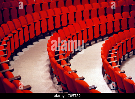 Curved rows of red seats in an auditorium. - Stock Photo