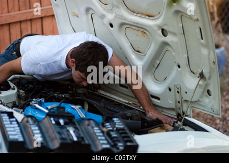 Man working on car in yard. Do it yourself mechanic performing auto repair. Examining engine compartment for signs - Stock Photo