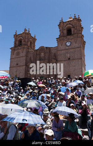 A large crowd of spectators sits infront of Puno Cathedral to watch the parade. - Stock Photo
