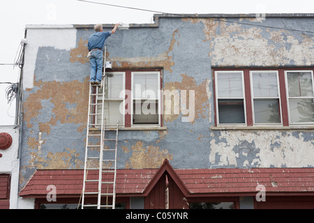A new coat of paint on an old building. A painter up a tall ladder applies a fresh coat of white paint to a badly - Stock Photo