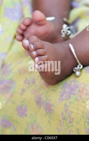 Indian babies bare feet with ankle bracelets against mothers sari. Andhra Pradesh, India - Stock Photo