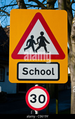 Road sign warning of children crossing near a school, and 30 speed limit in force. - Stock Photo
