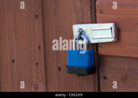 A plastic-coated padlock on a shed door.  Padlocks are useful to deter casual thieves. - Stock Photo