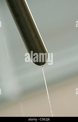 Rain water flowing from a drain pipe - Stock Photo