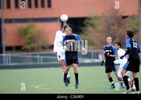Players use headers in an attempt to gain possession of the ball during a high school soccer match. USA. - Stock Photo