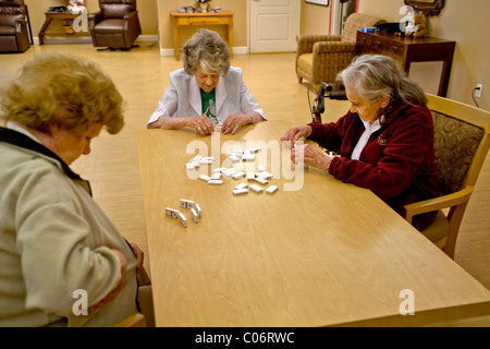 Three patients at a retirement home in Mission Viejo, California, play dominoes indoors. Note auto lift chairs in - Stock Photo