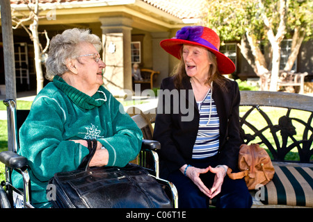 Two patients at a retirement home in Mission Viejo, California, chat outdoors on a sunny day. - Stock Photo