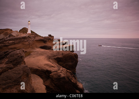 Lighthouse perched on rocks above a dark sea and a single fishing trawler on route to the fishing grounds. - Stock Photo