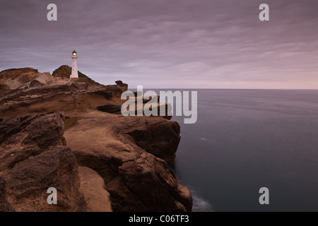 Lighthouse perched on rocks above a dark sea. The lighthouse is close to the village of Castlepoint in New Zealand. - Stock Photo