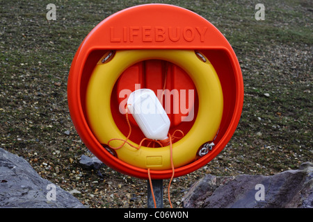 A yellow lifebuoy inside a bright orange red stand, and situated on the shingle beach at Barton on Sea. - Stock Photo