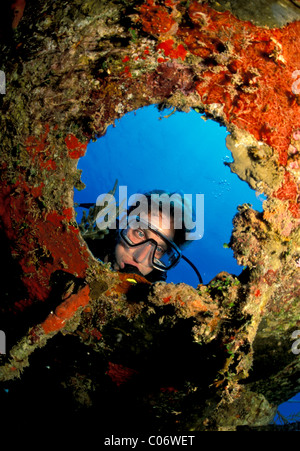 Scuba diver peers through porthole on sunken ship, Roatan, Honduras. - Stock Photo